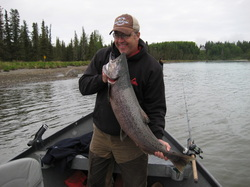 Happy fisherman present trophy King Salmon caught on the Kenai River in Alaska.