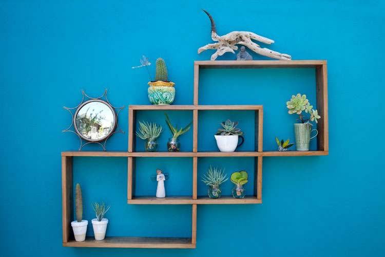 Reclaim Design's geometric shelving made from reclaimed wood containing angel statue, mirror, ornaments and plants.