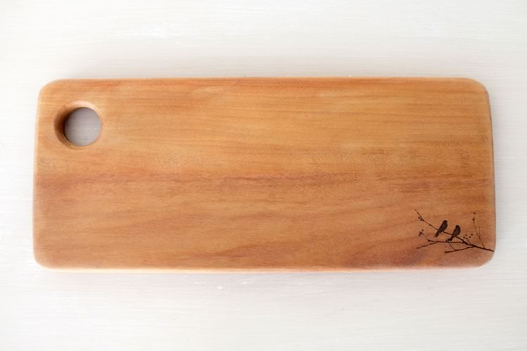Reclaim Design's lazer etched breadboard made from reclaimed wood with birds on branch design.