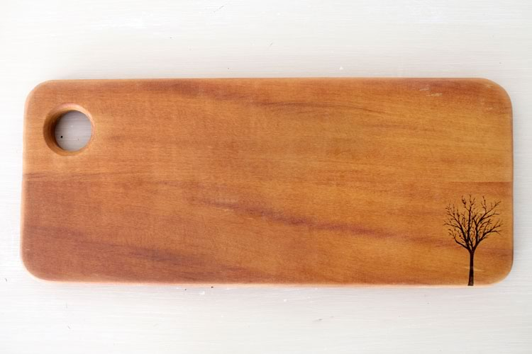 Reclaim Design's lazer etched breadboard made from reclaimed wood with tree design.