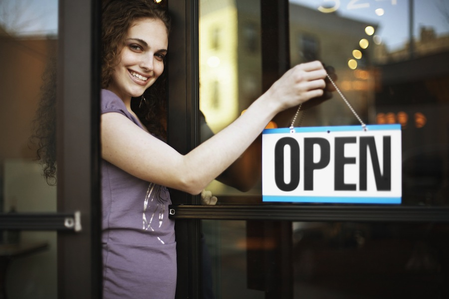 Small business owner with open sign on door
