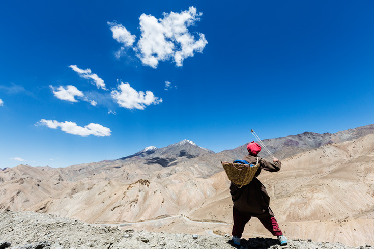 Woman slinging stones into a canyon in Ladakh, India