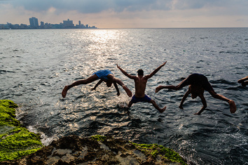 Boys jumping off the sea wall in Havana, Cuba