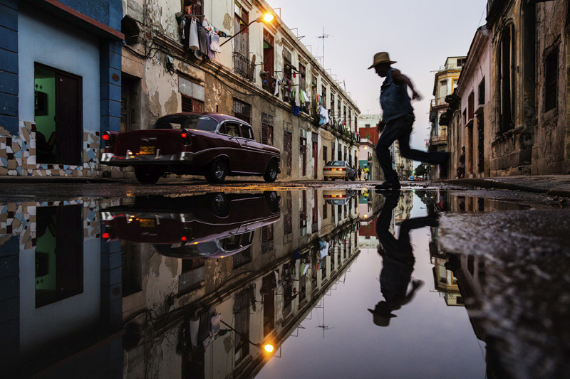 Man jumping over puddle in street in Havana, Cuba
