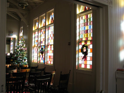 Photo of the sanctuary at Christmas time. Kenwood Community Church in Kenwood, California. Stained glass windows, cushioned wooden Windsor chairs, a piano, gabled ceiling, Christmas tree and Christmas wreaths.