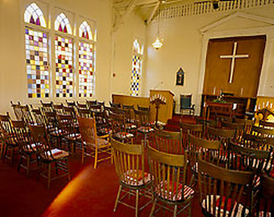 Photo of the sanctuary at Kenwood Community Church in Kenwood, California. Stained glass windows, elegant raised chancel and simple white cross, plush red carpet and cushioned wooden Windsor chairs, fresh flowers, taper candles, a piano and an organ.